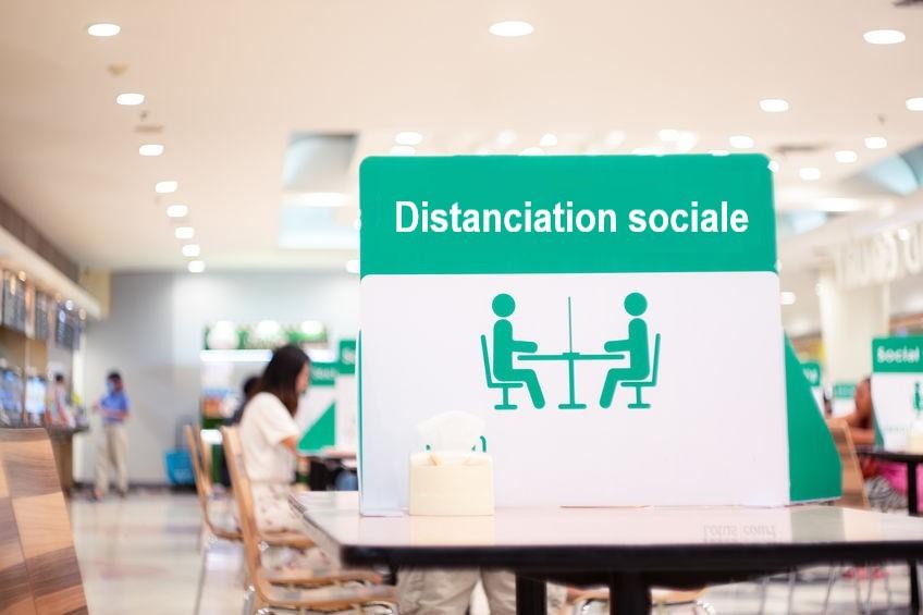 Photo d'un réfectoire avec des employés et d'un panneau en premier plan informant du respect de la distanciation sociale